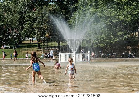 Boston, MA, USA 06.09.2017 - Families Children and People Enjoy the Cooling Spray at the Frog Pond on a hot summer day in Boston Common Public Park