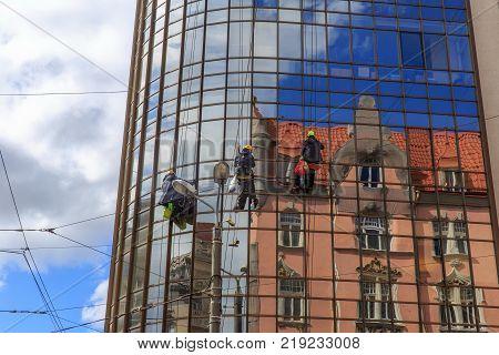 Washers wash the windows of modern skyscraper. Riga, Latvia