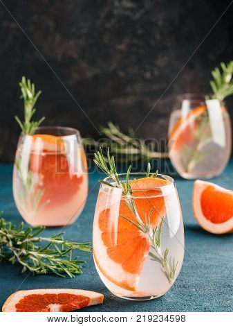 infused detox water or alcoholic or non-alcoholic cocktail with grapefruit and rosemary in glass on green and black cement background. healthy eating or holyday drink concept, copy space for text