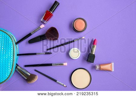 Makeup cosmetics tools background and beauty cosmetics products and facial cosmetics package lipstick eyeshadow on the purple background. Lifestyle Concept.