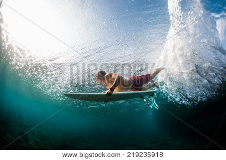Young surfer dives under the ocean wave and performs trick named in surfing as a Duck Dive