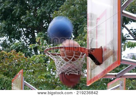 Motion of basketballs into hoop at park