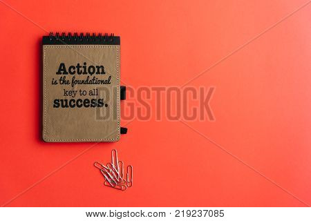 Lay flat of notebook with motivational quote and paperclips on bubble-gum pink background. Conceptual, success
