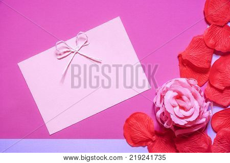 Pink rose  and a cute message card - Pink rose and red petals made of soap and a blank paper note with tied bow on a pink paper background. Perfect as an invitation or a greeting card.