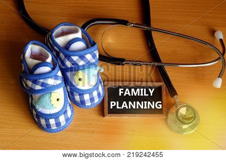 Family planning concept with stethoscope and cute blue baby shoes