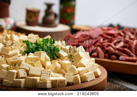 Close-up of big wooden plate, served with little cheese appetizer pieces and decorated with parsley leaves. There is tasty sausage set on the background. Tasty appetizers for strong alcohol drinks.