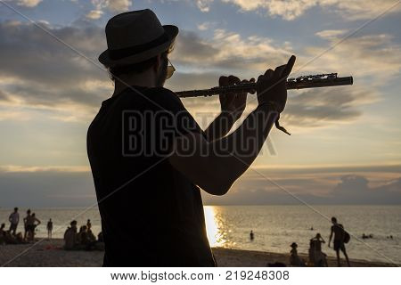 KOH PHANGAN THAILAND - JANUARY 14 2017: An unidentified musician man play the flute at sunset on the beach during a full moon party in island Koh Phangan Thailand