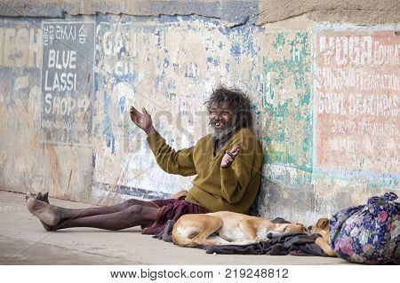 VARANASI INDIA - JANUARY 26 2017 : Poor man and dog on the ghats of the Ganges river in Varanasi India . Close up