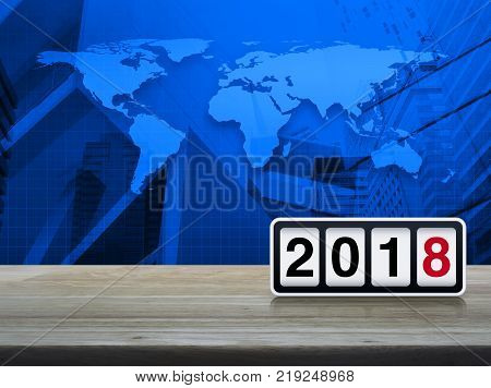 Retro flip clock with 2018 text on wooden table over world map and city tower Happy new year concept Elements of this image furnished by NASA