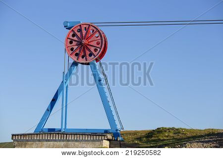 Close-up view of steel big wheel of cableway in Carpathian mountains against the blue sky Ukraine