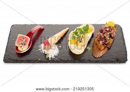 A serving of snacks with a fragrant gourmet fillings, with a beautiful serve on a slate board on a white background