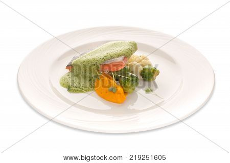 Molecular modern kitchen of red fish and vegetables under a frothy sauce on a white background