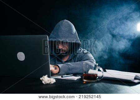 mysterious criminal man hides his face under the hood, doing something illegal on the laptop