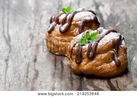 Belgian chocolate choux buns on wooden table