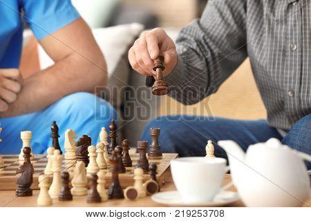 Young caregiver and senior man playing chess, closeup