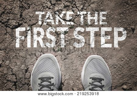 Take the first step text and sneakers on dry land top view