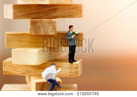 miniature people reading book on wood block stack Education and Business concept for growth success process.