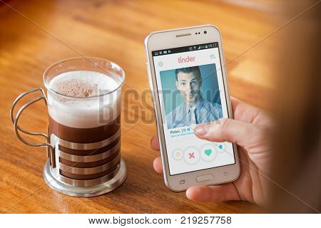 ROSARIO, ARGENTINA - AUGUST 12, 2017: Girl with a coffee cup. A smartphone in her hands with a tinder application on the screen. Young woman, millennial, Technology. Communications.