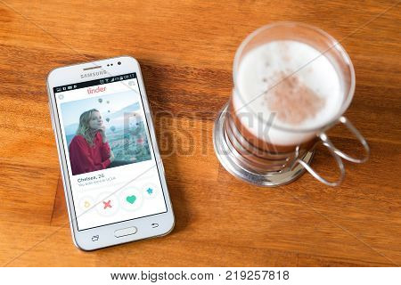 ROSARIO, ARGENTINA - AUGUST 12, 2017: Tinder application in the screen. Cell phone over a wood table near a coffee cup.