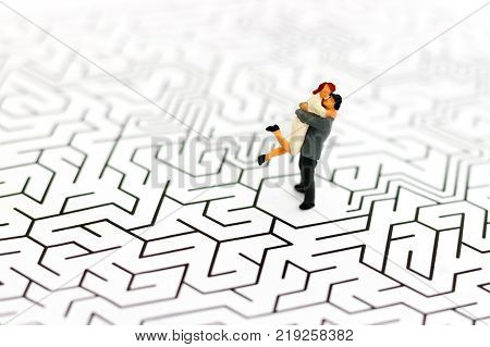 Miniature people Couple Lover standing center of maze Solve problems with love Concept. Miniature people: Businessman standing on center of maze with look at watch.. Concepts of finding a solution problem solving and challenge.
