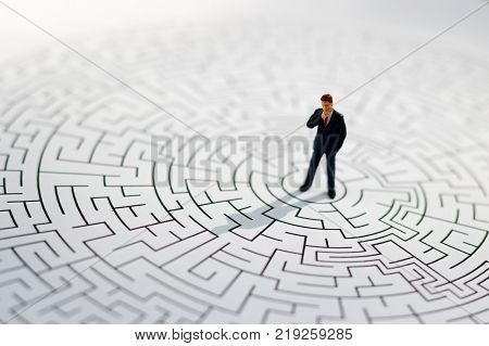 Miniature people: Businessman standing on center of maze. Concepts of finding a solution problem solving and challenge.