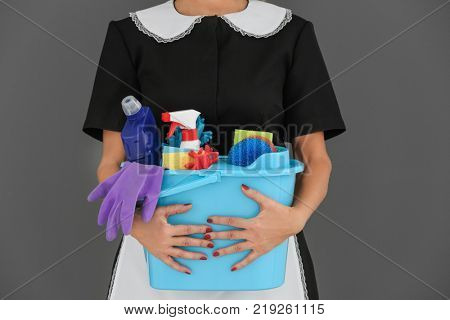 Charwoman with cleaning supplies on grey background, closeup