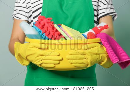 Woman with cleaning supplies on color background, closeup