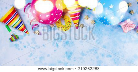 Bright colorful carnival or party border of balloons, streamers and confetti on blue table. Flat lay style, birthday or party greeting card with copy space and bokeh lights