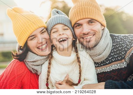 Happy girl with pigtails wears warm knitted sweater stands between father and mother laugh happilly have sincere smiles on their faces. Relaxed family have holidays spend nice time together