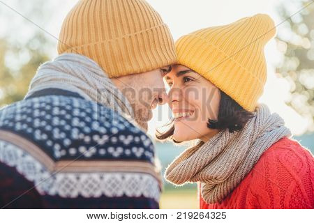 Adorable brunette female and her boyfriend stand closely to each other look at eyes smile happily as feel love and support. Good looking woman with scarf and hat has date with young attractive man
