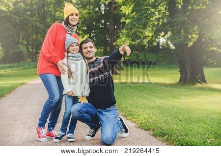 Pleasant looking dad shows with fore finger beautiful landscape to her daughter embraces her. Family of three members have walk at park have good relatioship look into distance as notice something