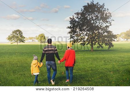 Three friendly family members have walk together on green meadow keep hands have pleasant conversation enjoy togetherness and beautiful landscapes look into distance stand backs to camera