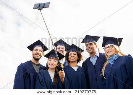 education, graduation, technology and people concept - group of happy international students in mortar boards and bachelor gowns taking picture by smartphone selfie stick outdoors