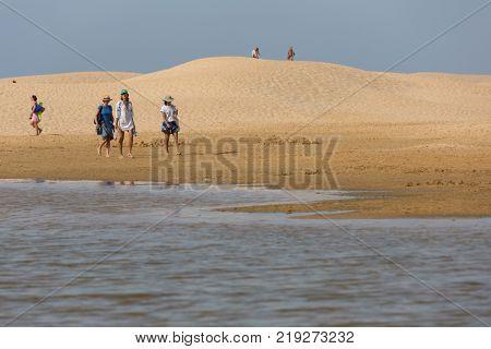 PRAIA DA BORDEIRA, PORTUGAL - AUGUST 20, 2017: People at the dunes of the beach of Praia da Bordeira. This beach is a part of famous tourist region of Algarve.