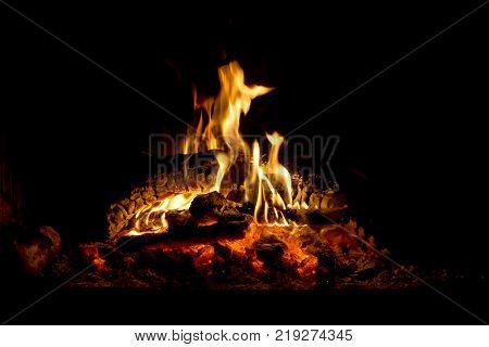 Burning fireplace in the winter season. The firewood burning in fireplace close-up