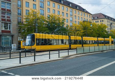 Yellow tram in the city center of Dresden. City transport of Europe.