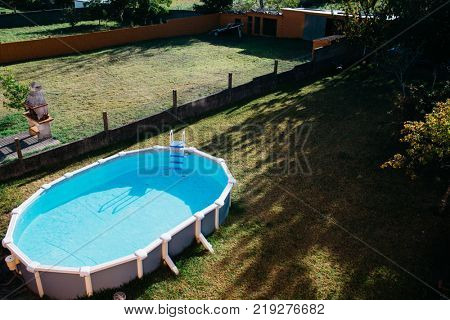 An above ground pool sets on grass in the backyard on a sunny summer day aerial view