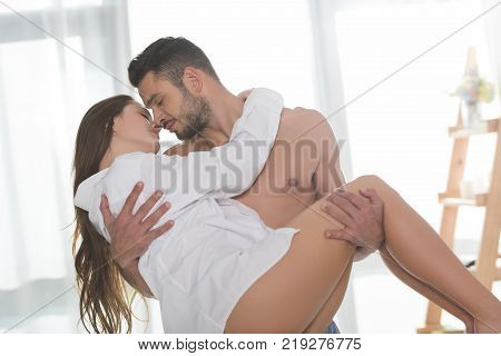 handsome shirtless man carrying his beautiful girlfriend in white shirt