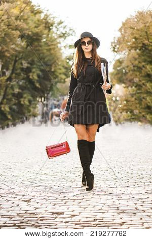 Beautiful Attractive Brunette Girl in Sunglasses and black dress Walking with Vogue Journal by the Sunny Street