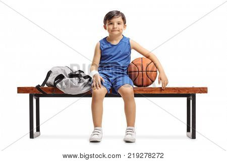 Little basketball player sitting on a wooden bench next to a sports bag isolated on white background