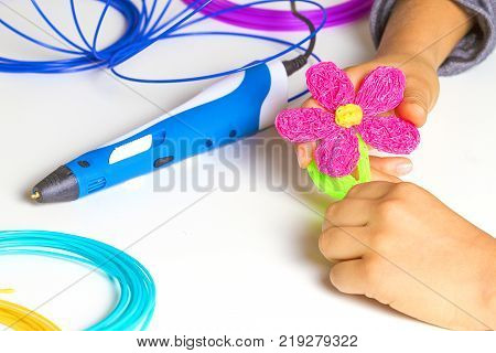 Kid hands creating with 3d printing pen, colorful filaments on white desk.