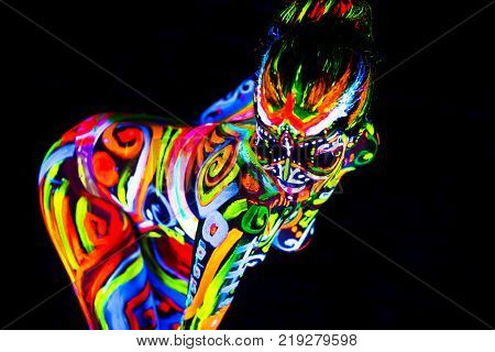 An attractive young girl in bright blacklight bodyart glowing in darkness