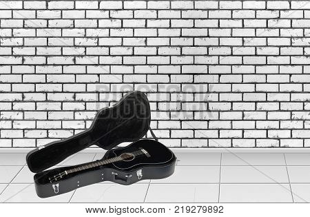 Home interior - Acoustic guitar in hard case in front on a brick wall background