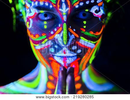 Close-up Portrait of an attractive young praying girl in bright blacklight bodyart