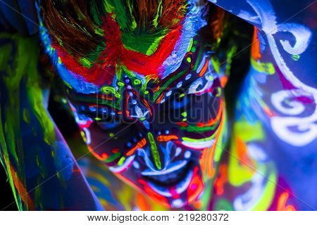 Close-up Portrait of an attractive young girl in bright blacklight bodyart poster