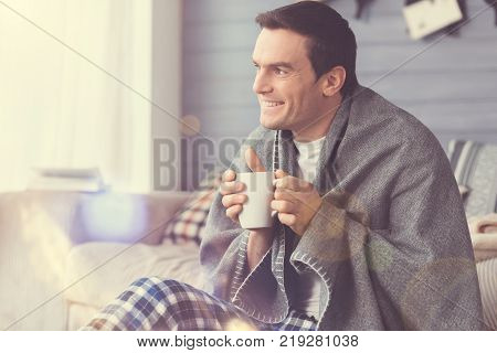 Lovely moment. Nice attractive positive man sitting in the living room wrapped in blanket and drinking coffee