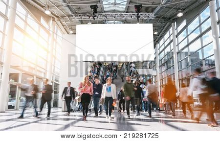 View of blurred crowd on a exhibition with trade fair booths. copyspace for your individual text.