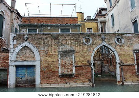Weathered facade of Venice palace on canal. Old walls of italian houses. Renaissaince entrance into venetian palace.