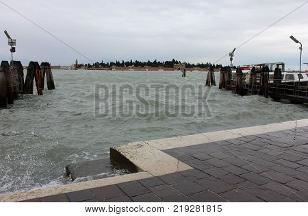 Venice quay with wooden stage poles. Bank of Venice quay in winter. Sea bank of Venice in gray day.