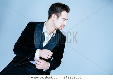 Portrait of a young handsome man in a suit, looking to the side, against plain studio background, buttons undone